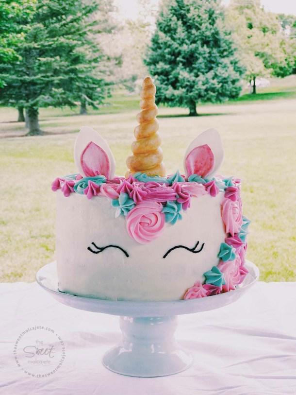 Pastel de Unicornio sobre cake stand de cerámica, en una fiesta de cumpleaños en el parque