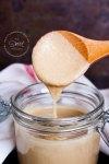Salsa Tahini casera en un frasco de cristal con una cucharita de madera, la cucharita está sacando un poco de tahini de frasco y la salsa escurre de la cuchara.