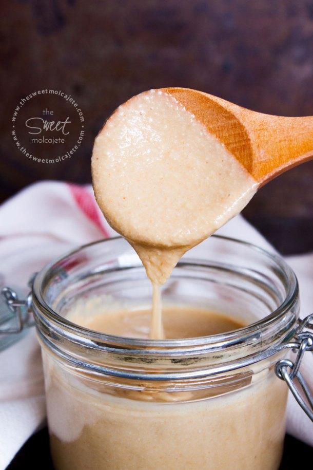 Salsa Tahini casera en un frasco de cristal con una cucharita de madera sacando un poco de salsa del frasco. Se ve la salsa tahini escurriendo de la cuchara.