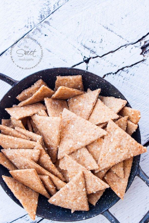 Imagen de un platito pequeño de peltre negro lleno de galletitas saludables saladas en forma de triangulo sobre tablas de madera blancas - 15 ideas de snacks saludables