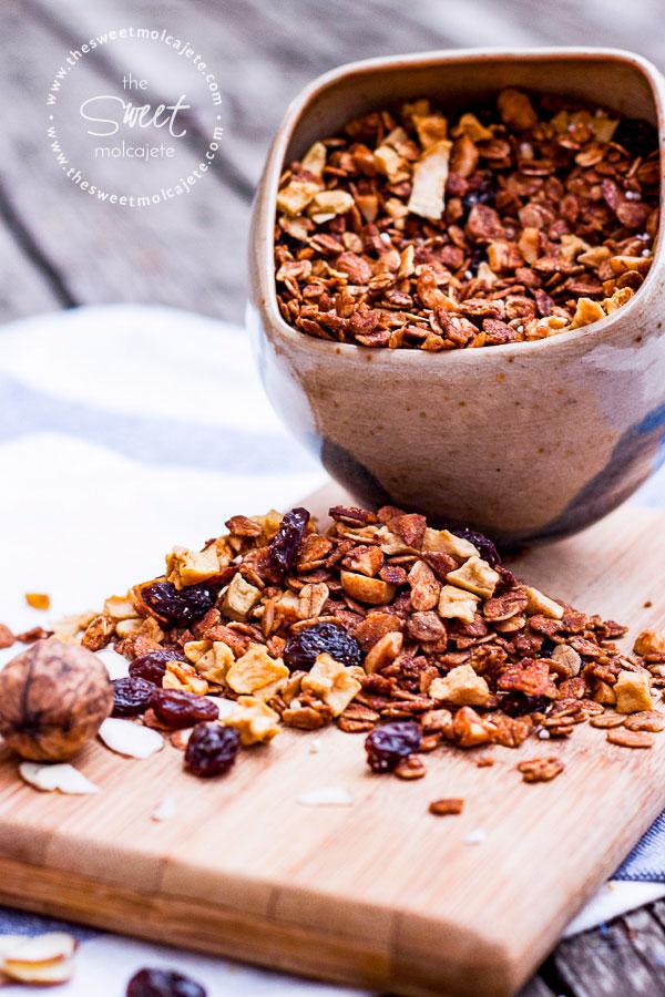 Imagen de una tazita de cerámica u poco inclinada y llena de granola casera, hay granola casera en la mesa como que se rebosó de la taza - 15 ideas de snacks saludables