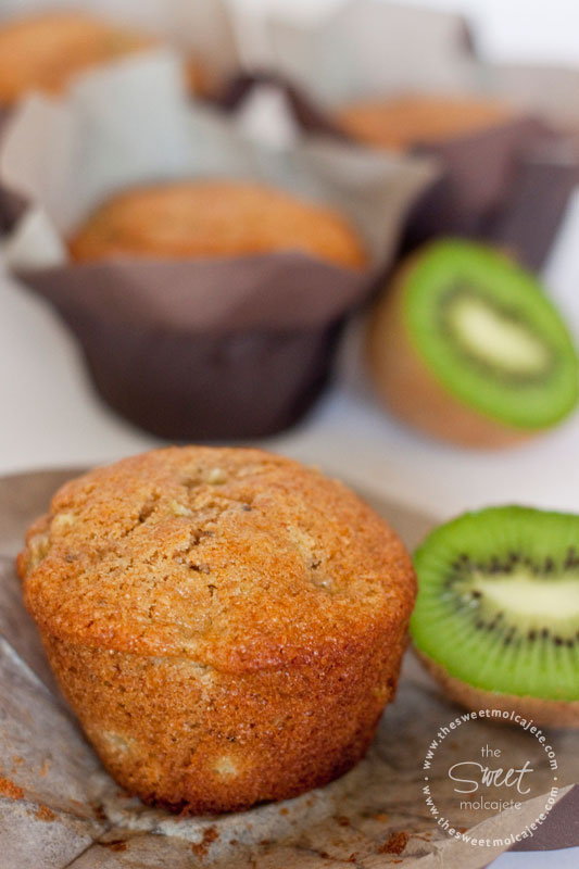 Imagen de un Muffin Integral de Kiwi con un kiwi partido a la mitad a lado. Al fondo se ven un poco borrosos más Muffins Integrales de Kiwi - 15 ideas de snacks saludables