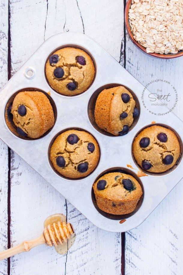 Imagen de una charola llena de Muffins de Avena con Moras sin gluten. Se ve un plato lleno de aven a un lado y una palita con miel del otro - 15 ideas de snacks saludables
