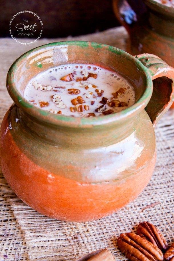 Atole Nuez con nuez picada en la superficie en una taza de barro mexicana