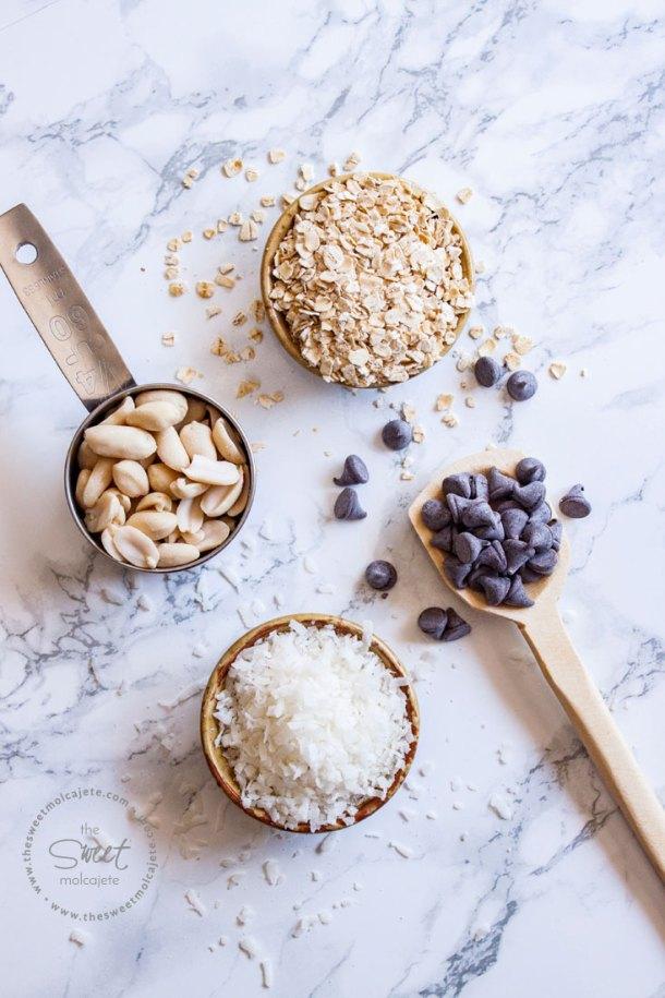Una taza medidora con cacahuate, un tazón pequeño con avena y otro con coco y una cuchara de madera con chispas de chocolate oscuro.