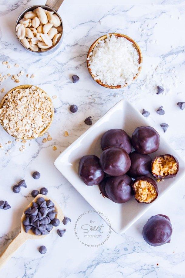 Vista aérea de Bolitas de Cacahuate con Chocolate sobre un plato donde hay una bolita mordita, alrededor se ven los ingredientes utilizados