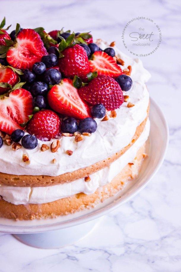 Acercamiento a un pastel de tres leches en dos capas relleno y cubierto de crema batida con fresas, moras y nueces