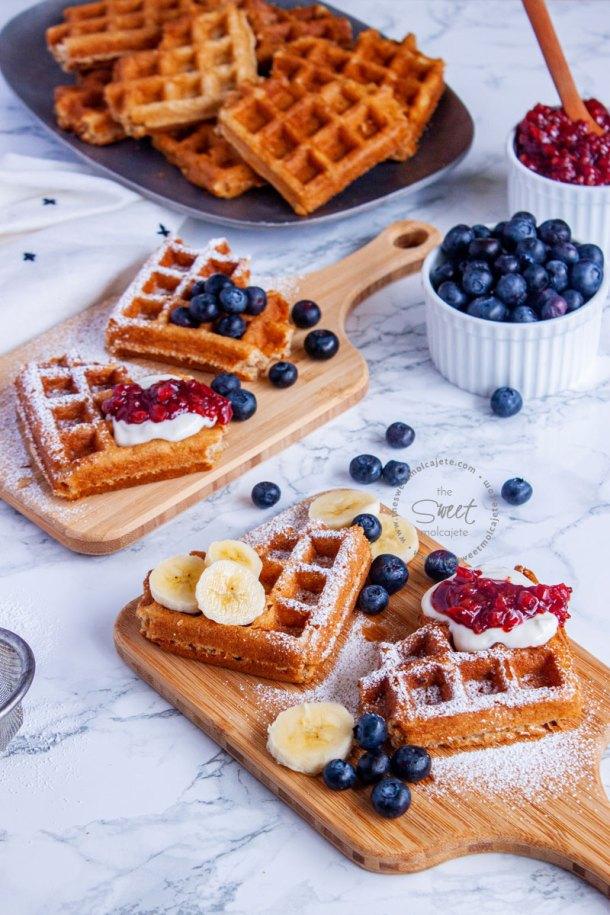 dos tablitas con waffles de corazon decorados con fruta, azucar glass, crema batida y mermelada