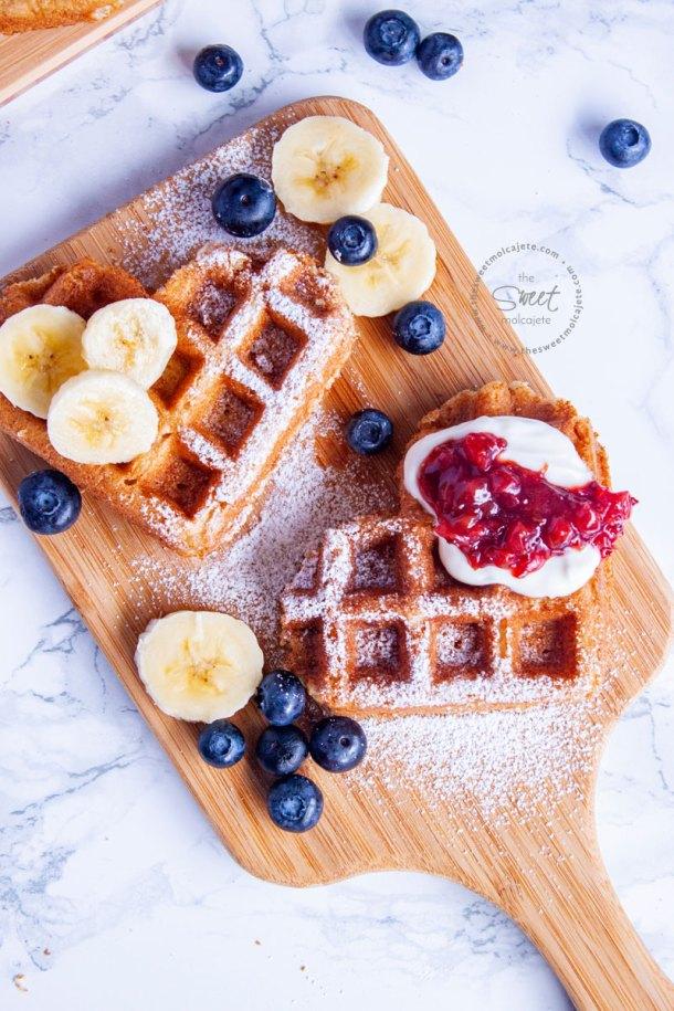 2 waffles de corazon en una tablita con platano, moras, crema batida y mermelada
