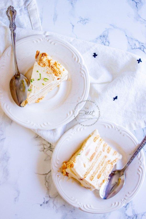 Dos rebanadas de pastel helado Carlota de Limón en platitos blancos con cucharas de plata