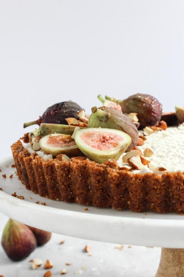 Side angle of a no-bake honey mascarpone fig tart on a cake stand