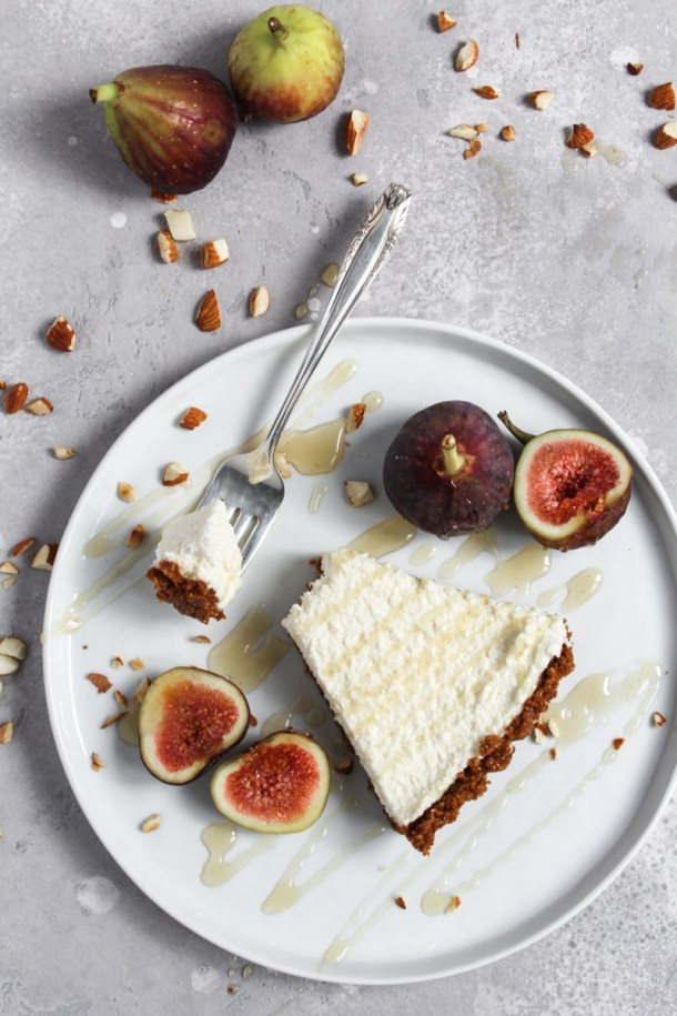 Slice of no-bake honey mascarpone fig tart on a plate with fresh figs for garnish.