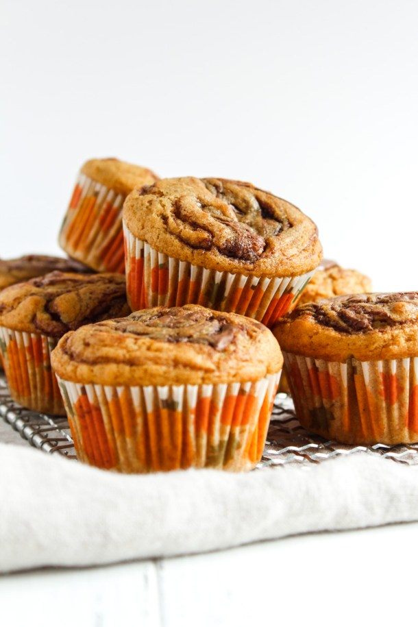 8 pumpking Nutella muffins arranged in a two layer stack over a linen napkin.