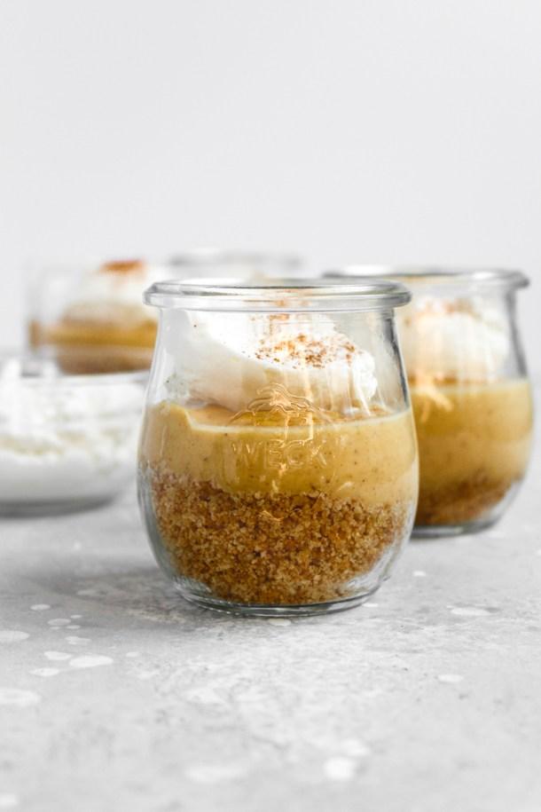 Jars of pumpkin custard with layers of graham cracker, custard, and whipped cream.