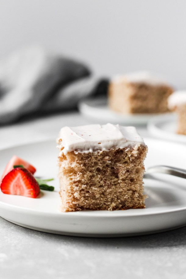 Slice of fresh strawberry sheet cake with strawberry cream cheese frosting in a dish