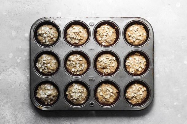 Batter portioned into muffins tins for banana muffins topped with raw oats.