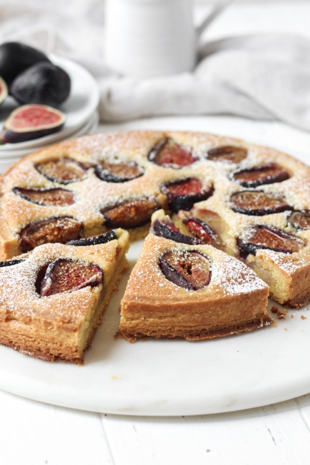 Fresh fig tart with an almond cream filling with two slice cut.