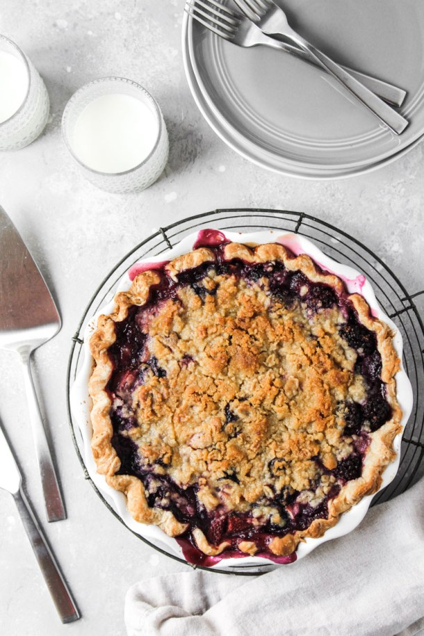 Mixed berry pie with crumb topping in pie dish on cooling rack looking from overhead.