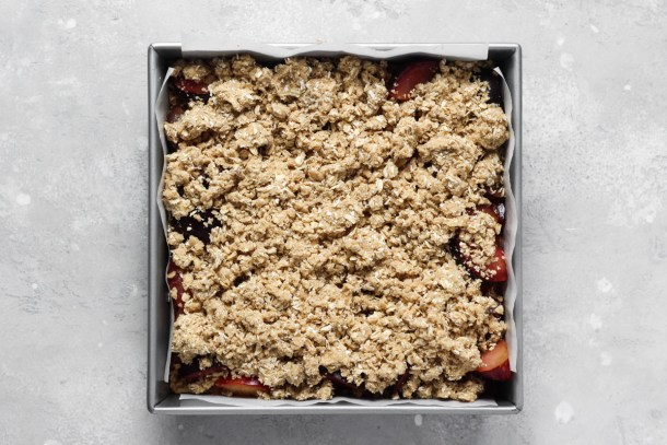 Unbaked plum bars in square baking pan.