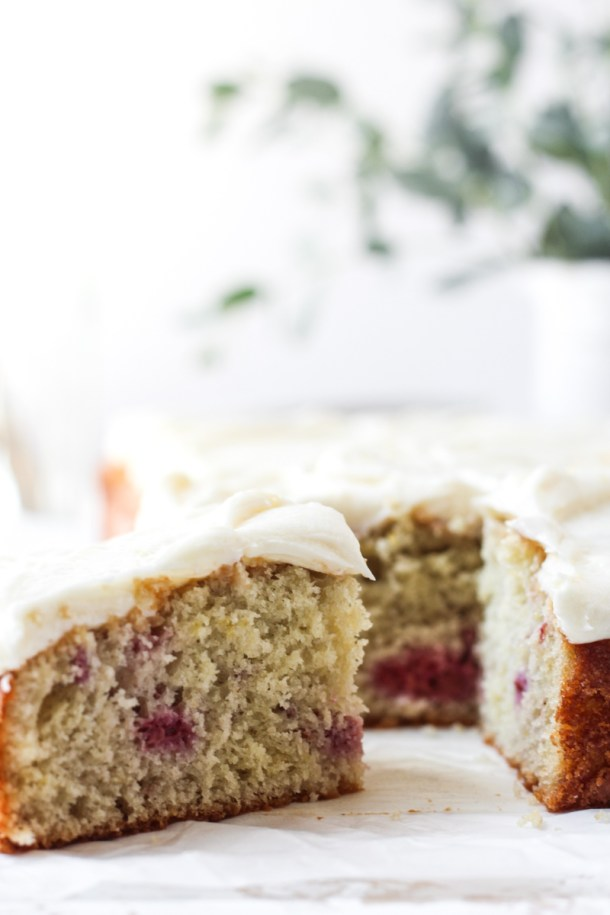 Rasberry sheet cake with lemon mascarpone frosting with large slice cut.