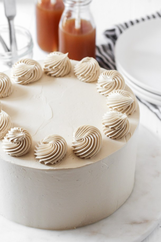 Looking over an 8-inch round apple cider cake with brown sugar Swiss meringue buttercream with rosettes on top and apple cider in the background.