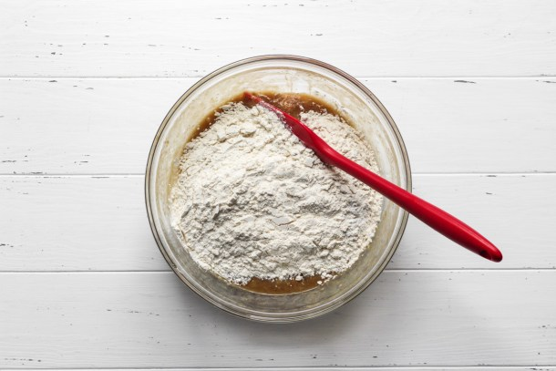 Banana bread cookie dough wet ingredients topped with dry ingredients in a glass bowl with a red spatula.