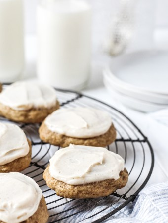 Banana bread cookies topped with cream cheese frosting on a French round wire rack with milk and plates in the background.