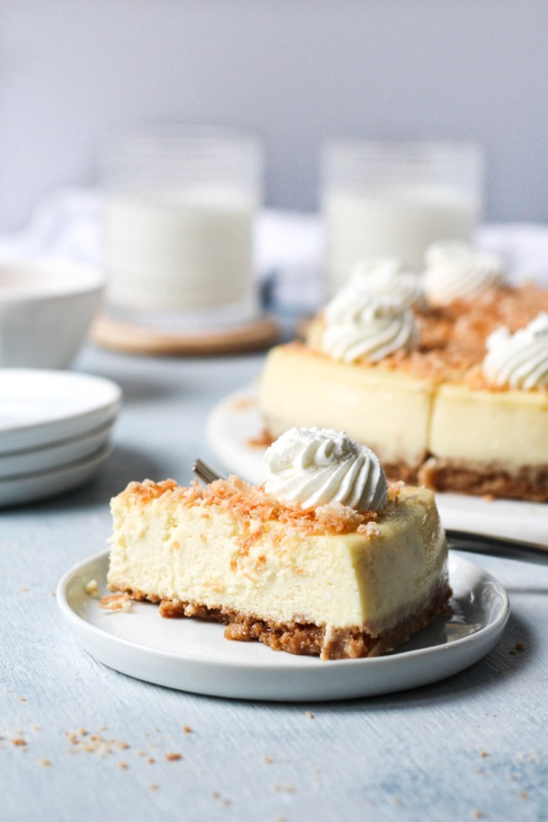 Slice of coconut cheesecake in a plate topped with toasted coconut and a dollop of whipped cream. Whole cheesecake and glasses of milk in the background.