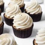 Several coffee cupcakes with coffee buttercream on a white wood board for display.