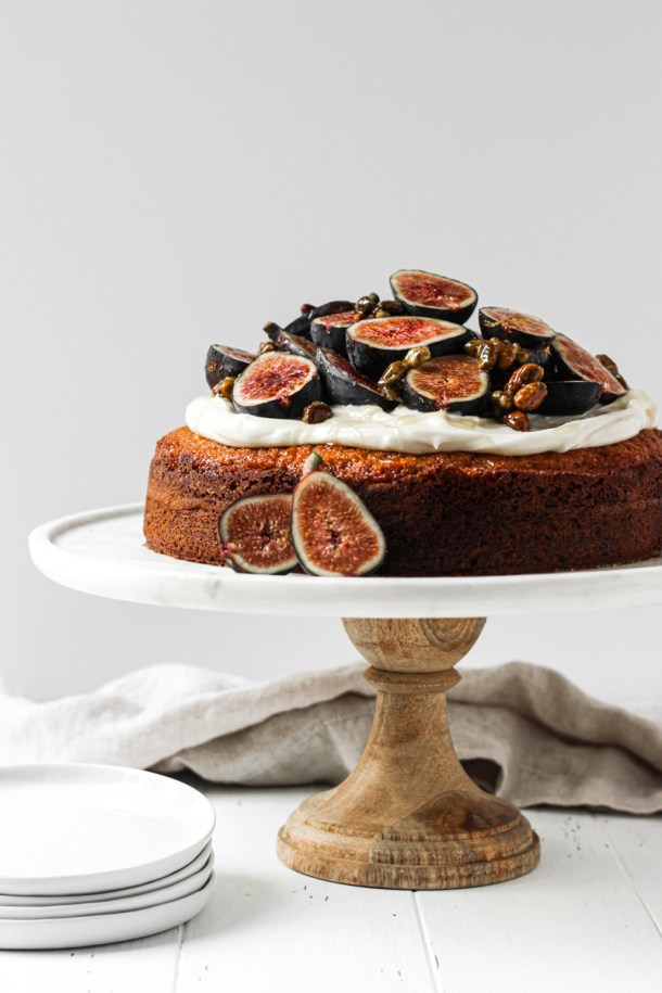 Fig cake with fresh seasonal figs, cream cheese frosting, honey and nuts on a cake stand.
