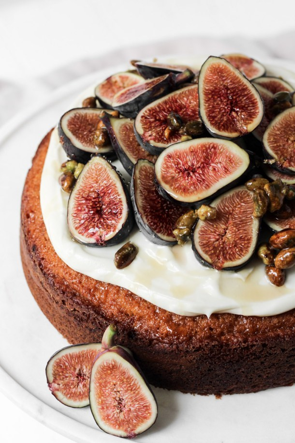 Close up of fig cake with fresh seasonal figs, cream cheese frosting, honey and nuts on a cake stand.