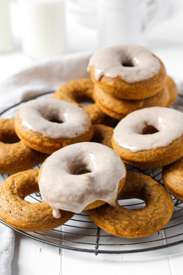 Stack of baked pumpkin donuts some with glaze on a round French wire rack.