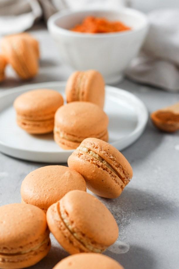 Spread of pumpkin macarons filled with pumpkin Swiss meringue buttercream.