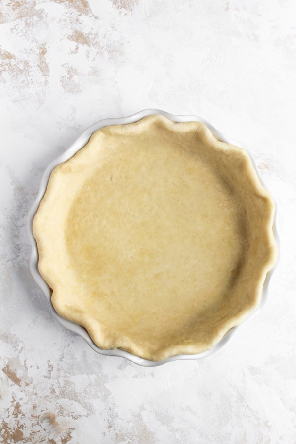 Unbaked all butter pie crust fitted in a pie plate for brown butter pumpkin pie.