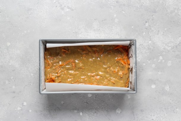 9x5 -inch baking pan lined with parchment paper and filled with carrot cake loaf batter.