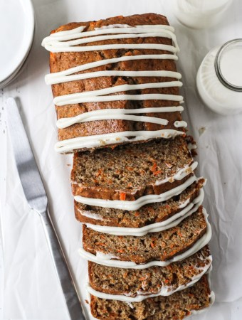 Overhead shot of carrot cake loaf sliced with zig zag drizzle of homemade cream cheese frosting.