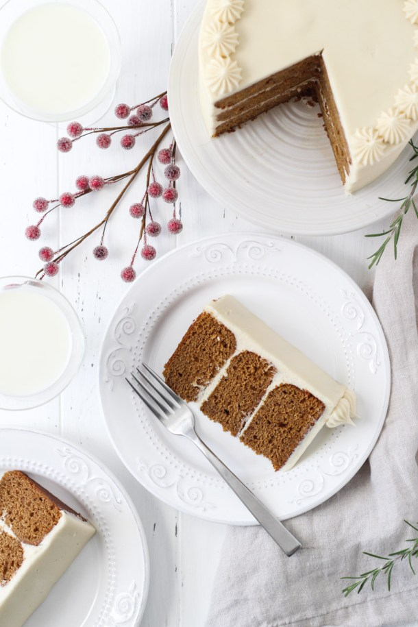 Overhead shot of gingerbread layer cake with two slices on a plates and the cake on a white cake stand.