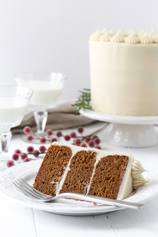 Slice of gingerbread layer cake on a plate with cake in the background on a white cake stand.