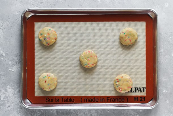 Sheet pan with 5 unbaked funfetti cookies stuffed with buttercream.