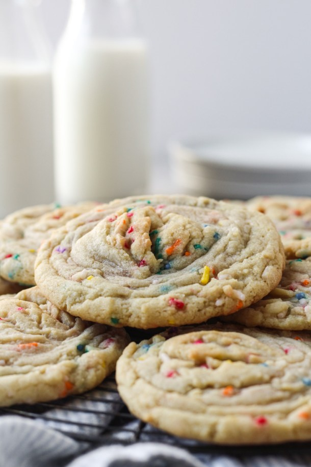Stack of funfetti stuffed cookies with buttercream with milk and dishes in the background.