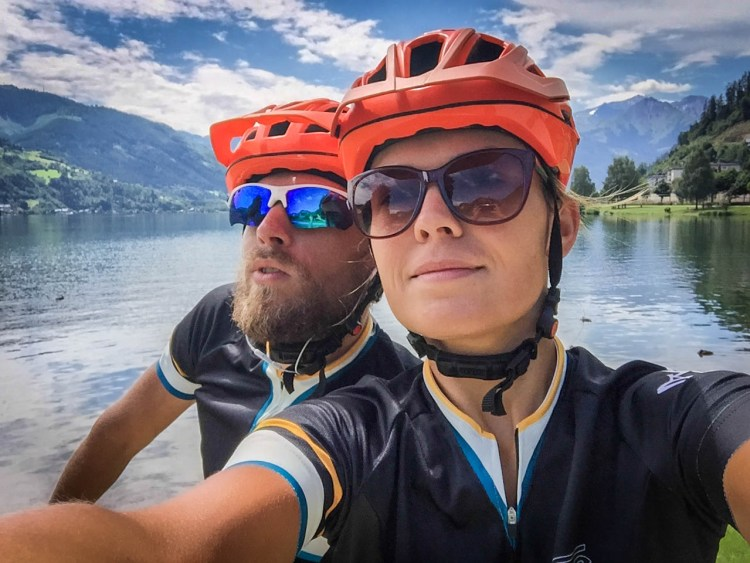 selfie of smiling bicycle couple with orange helmets at lake