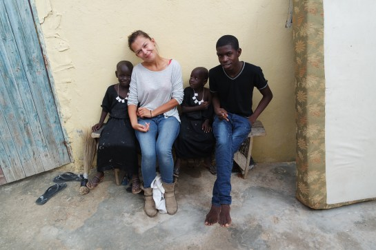 A white woman traveling Mauritania sitting next to three African brother on a bench