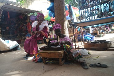 two woman sitting in a West African Craft market