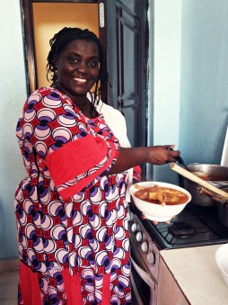 smiling African woman with colorful clothes cooking