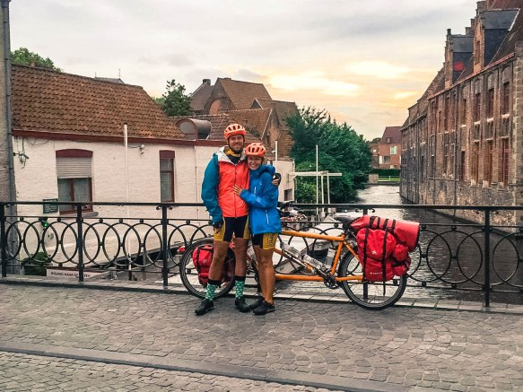 A couple next to a tandem bicycle on a bridge in Bruges, Belgium