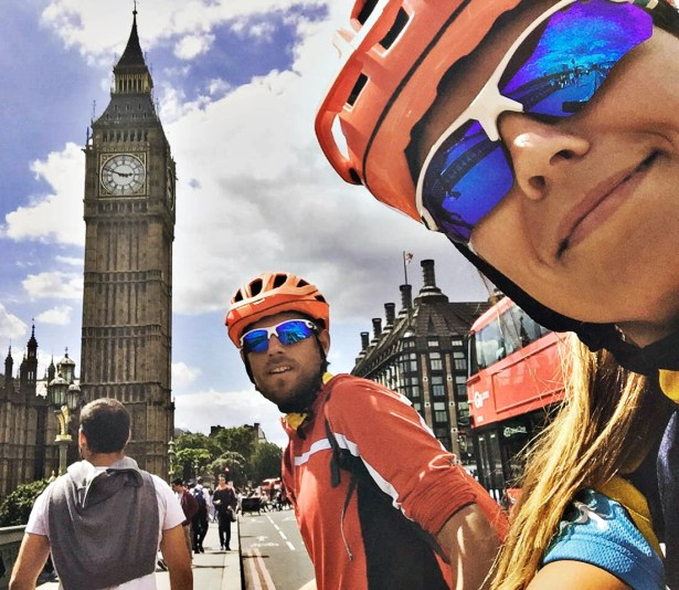 A male bicycle rider and a female bicycle rider in front of Big Ben, in the United Kingdom