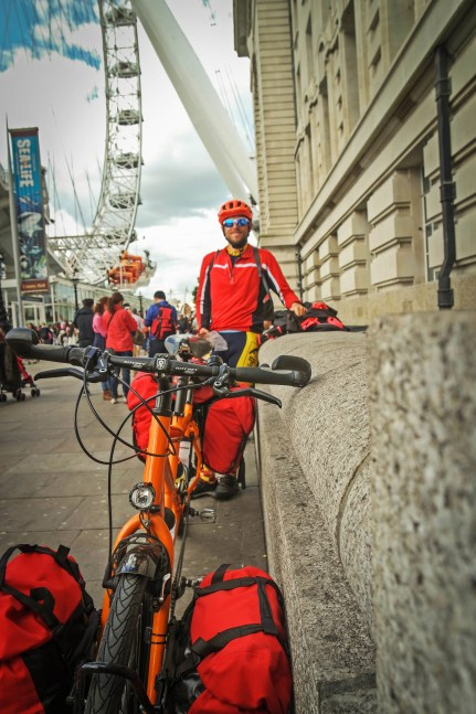 Male bicycle rider standing on a wall behind a tandem bicycle and in front of the London eye, in the United Kingdom