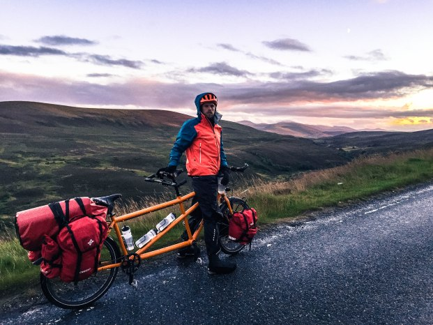 A male bicycle rider on a orange tandem bicycle,cycling the Scottish Highlands