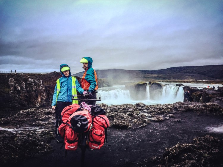 A couple with a tandem bicycle at the Godafoss Waterfalls, Iceland