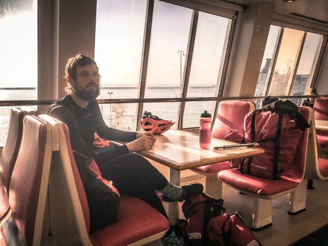 A bearded man sitting on a seat at a ferry to Wales